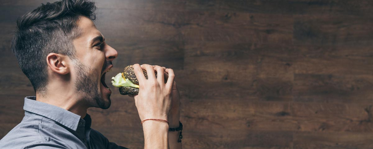 young man about to bite into a hamburger - the sound of which can be a major trigger for those with misophonia