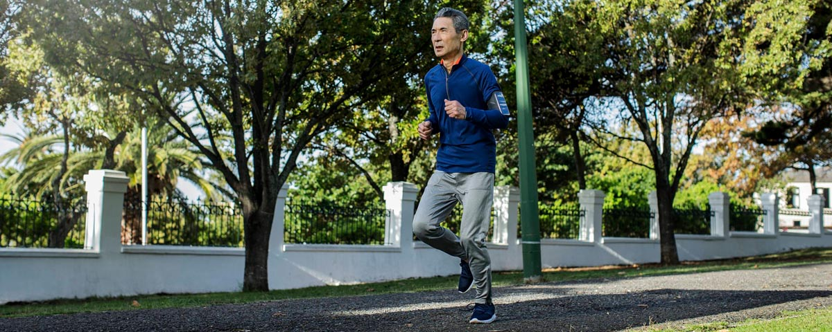 Man exercising with MFi hearing aids - running while streaming music directly from his phone