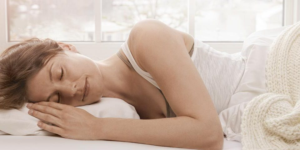 A woman sleeping while wearing Phonak Lyric hearing aids, which stay in your ears 24/7 for months at a time.