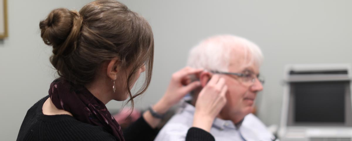 Audiologist putting a new hearing aid in an ear